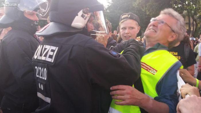 PolizistGreiftLinkenOrdnerAn